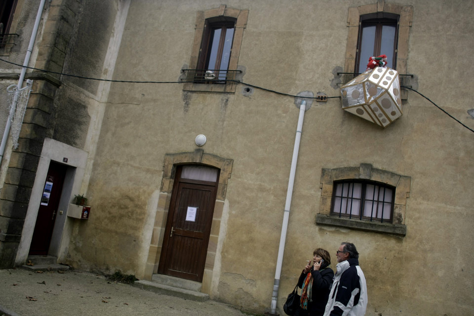 People walk past a model meant to represent a UFO hanging outside a window in the town of Bugarach, France, Thursday, Dec. 20, 2012. The clock is ticking down to Dec. 21, the supposed end of the Mayan calendar, and from China to California to Mexico, thousands are getting ready for what they think is going to be a fateful day. The sleepy town of Bugarach, nestled in the French Pyrenees mountains, is bracing for the arrival of hundreds of New Age enthusiasts and UFO believers that want to witness the end of the Mayan Long Count calendar. (AP Photo/Marko Drobnjakovic)