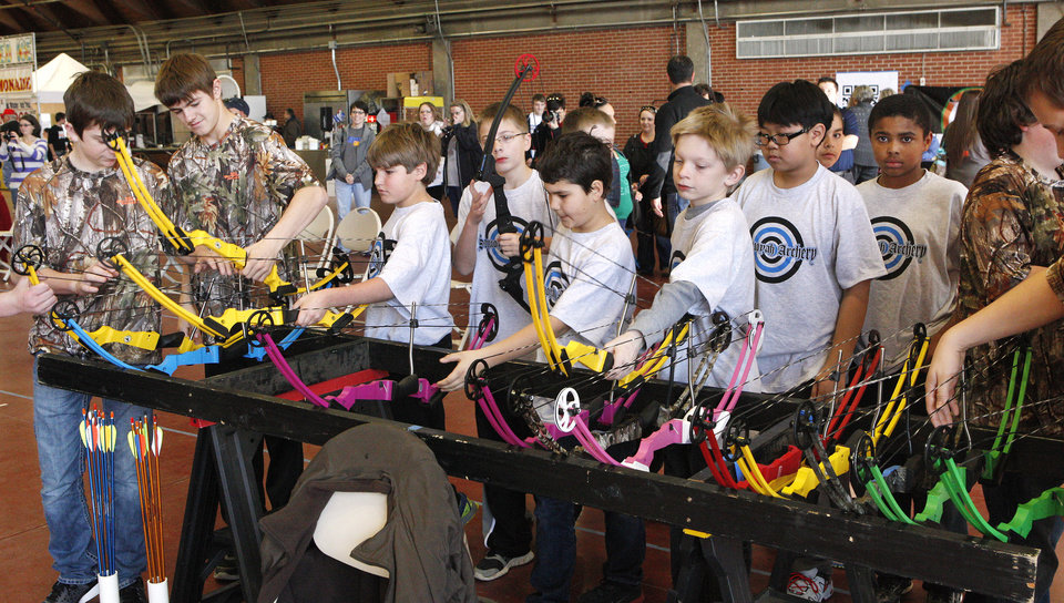"Students select their bows from a rack while participating in a regional ""Oklahoma Archery In The Schools"" shoot at State Fair Park in Oklahoma City Thursday, Feb. 14, 2013. Photo by Paul B. Southerland, The Oklahoman"