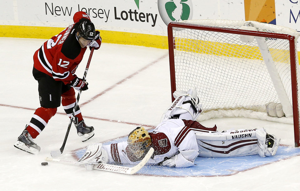 Photo - Phoenix Coyotes goalie Thomas Greiss, right, of Germany, lays out to block a shot by New Jersey Devils ring wing Damien Brunner, of the Czech Republic, during a shootout in an NHL hockey game, Thursday, March 27, 2014, in Newark, N.J. The Coyotes won 3-2. (AP Photo/Julio Cortez)