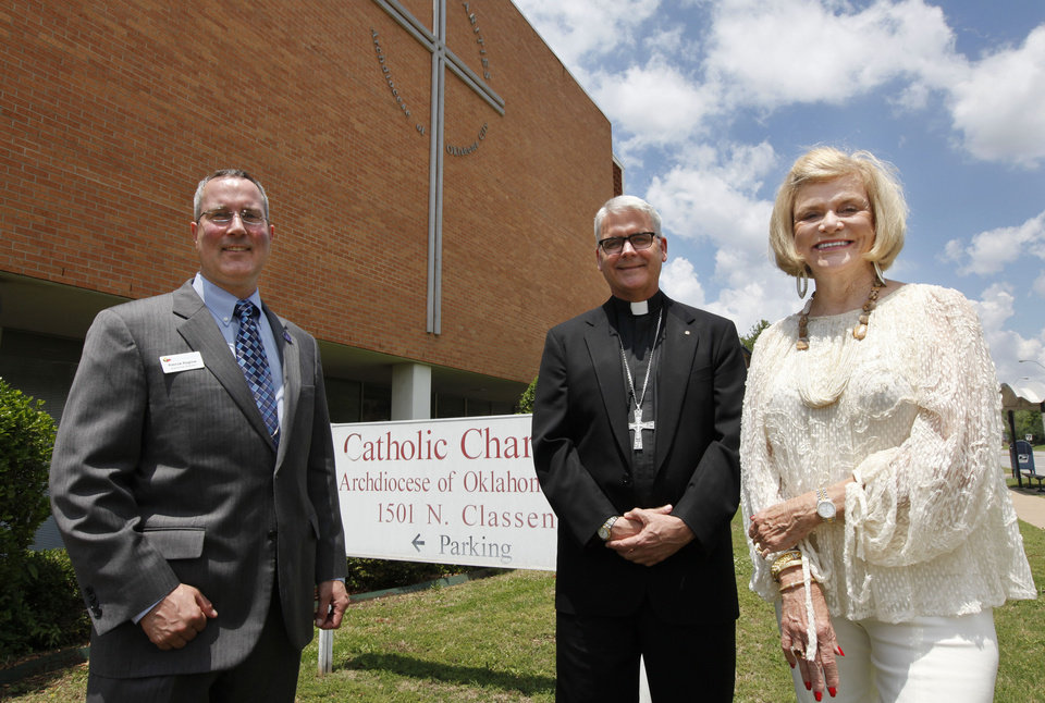 Photo - Patrick Raglow, left, executive director of Catholic Charities, Oklahoma City Archbishop Paul S. Coakley, and Crossbeam campaign co-chair Judy Love talk Thursday in front of the current Catholic Charities home at 1501 N Classen Blvd. in Oklahoma City.  Photo by Paul Hellstern, The Oklahoman   PAUL HELLSTERN