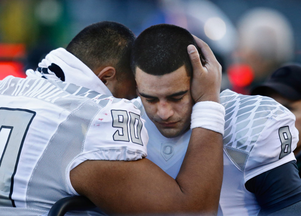 Photo - Oregon quarterback Marcus Mariota (8) is comforted by defensive tackle Ricky Havili-Heimuli (90), after Mariota was looked at by medical personnel after in the final minutes of an NCAA college football game against Arizona in Tucson, Ariz., Saturday, Nov 23, 2013. (AP Photo/The Oregonian, Thomas Boyd)  MAGS OUT; TV OUT; LOCAL TV OUT; LOCAL INTERNET OUT; THE MERCURY OUT; WILLAMETTE WEEK OUT; PAMPLIN MEDIA GROUP OUT