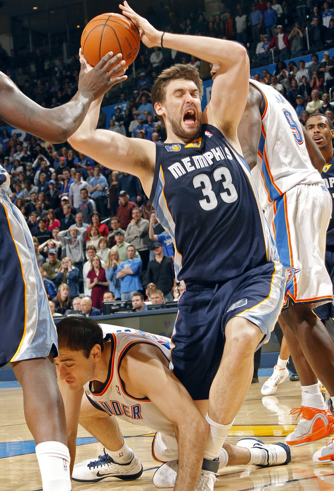 Photo - Memphis' Marc Gasol (33) is fouled by the Thunder's Nenad Krstic (12) during the NBA basketball game between the Oklahoma City Thunder and the Memphis Grizzlies at the Oklahoma City Arena on Tuesday, Feb. 8, 2011, Oklahoma City, Okla.Photo by Chris Landsberger, The Oklahoman