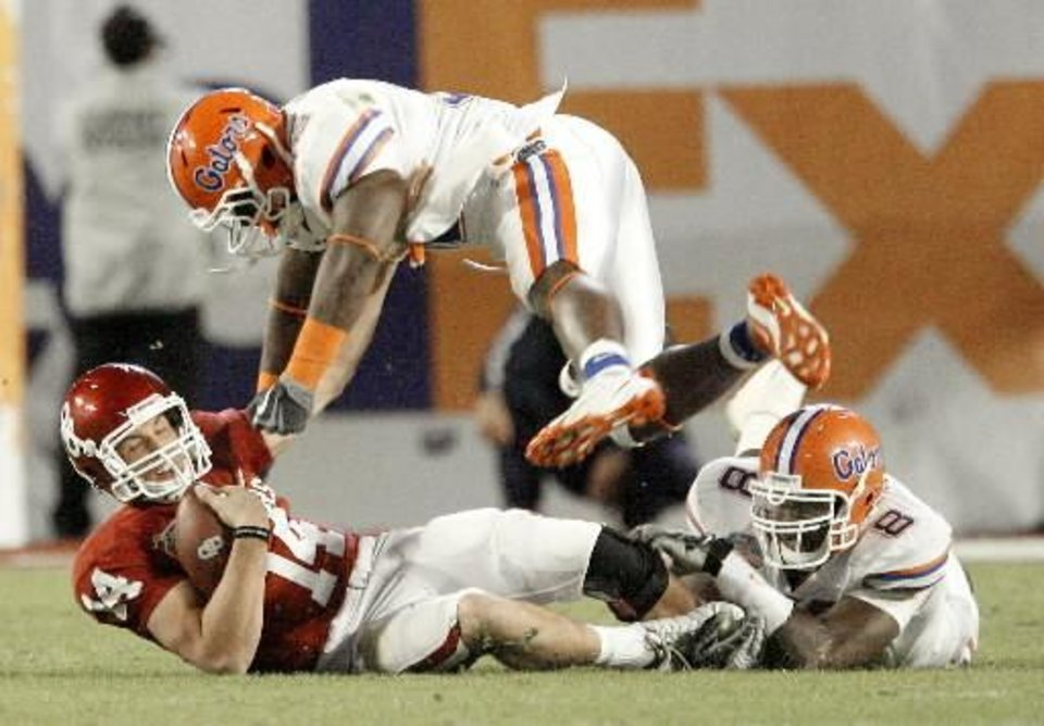 OU's  Sam  Bradford gets hit by Florida's Dustin Doe, center, and Carlos Dunlap during the second half of the BCS National Championship college football game between the University of Oklahoma Sooners (OU) and the University of Florida Gators (UF) on Thursday, Jan. 8, 2009, at Dolphin Stadium in Miami Gardens, Fla. By Bryan Terry