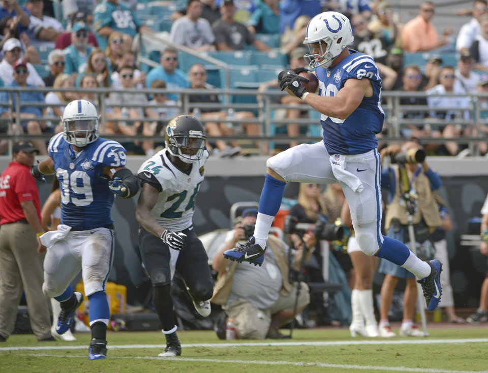 Photo - Indianapolis Colts tight end Coby Fleener (80) leaps across the goal line in front of Jacksonville Jaguars cornerback Will Blackmon (24) as teammate fullback Stanley Havili (39) looks, on a 31-yard touchdown pass play during the second half of an NFL football game against the Jacksonville Jaguars in Jacksonville, Fla., Sunday, Sept. 29, 2013..(AP Photo/Phelan M. Ebenhack)