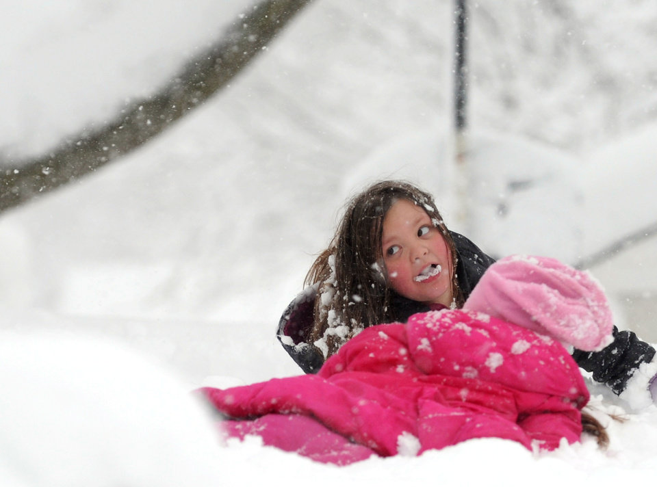 Photo - Ashton Lam, 8, comes up with a mouthful of snow while enjoying the winter weather in Staunton, Va., on Wednesday, March 6, 2012.  The March snowstorm is primarily hitting a region stretching from central Virginia to the northern and western portions of the state, where snow is piling up quickly.  (AP Photo/The News Leader, Mike Tripp) NO SALES