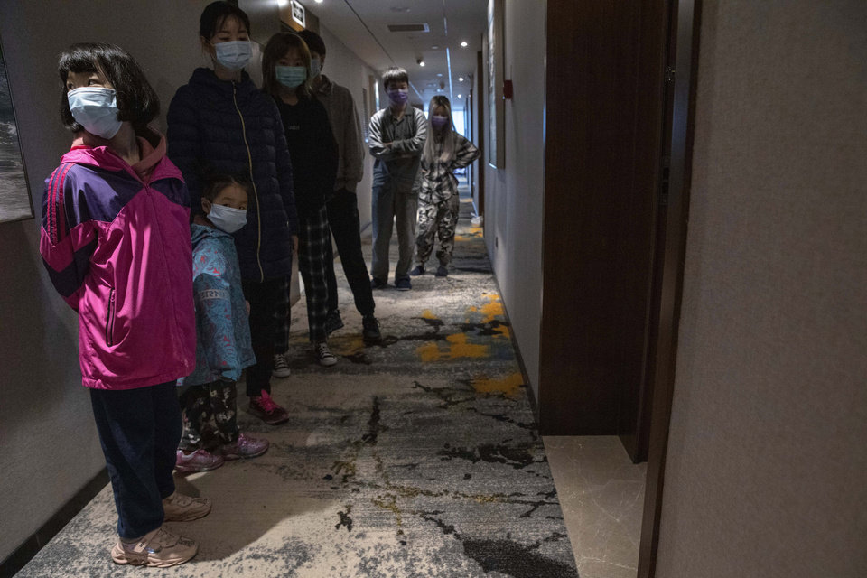 Photo -  Quarantined returnees queue up for a COVID-19 test at a quarantine hotel in Wuhan in central China's Hubei province on Tuesday, March 31, 2020. China on Tuesday reported just one new death from the coronavirus and dozens of new cases, claiming that all new cases came from overseas. (AP Photo/Ng Han Guan)
