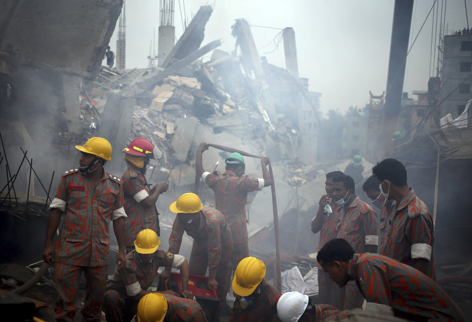 Photo - Workers and fire fighters are shrouded in smoke as they prepare to dislodge the debris and fallen ceiling of the garment factory building which collapsed in Savar, near Dhaka, Bangladesh on Monday, April 29, 2013. Rescue workers in Bangladesh gave up hopes of finding any more survivors in the remains of a building that collapsed five days ago, and began using heavy machinery on Monday to dislodge the rubble and look for bodies - mostly of workers in garment factories there. At least 381 people were killed when the illegally constructed, 8-story Rana Plaza collapsed in a heap on Wednesday morning along with thousands of workers in the five garment factories in the building.(AP Photo/Wong Maye-E)
