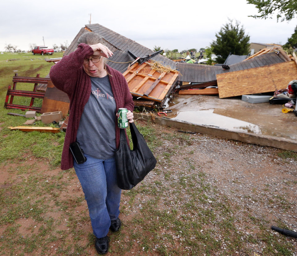 Photo - Denise Stark worries about a second storm as she walks past demolished buildings at her home after a tornado ripped through Bridge Creek, Okla. on Wednesday, May 6, 2015.  Photo by Steve Sisney, The Oklahoman