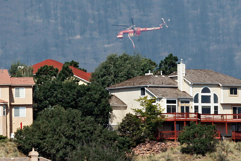 Photo -   A firefighting helicopter flyies over homes while battling the Waldo Canyon wildfire west of Colorado Springs, Colo., on Wednesday, June 27, 2012. Authorities say it remains too dangerous for them to fully assess the damage from a destructive wildfire threatening Colorado's second-largest city. (AP Photo/Ed Andrieski)