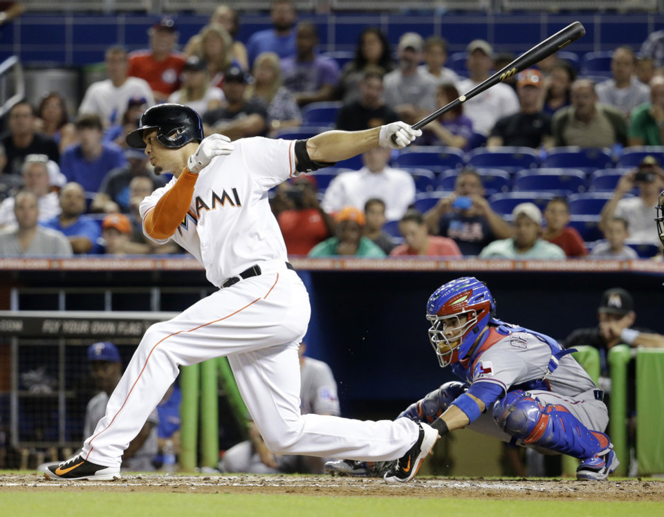 Photo - Miami Marlins' Giancarlo Stanton strikes out swinging in the third inning as Texas Rangers catcher Robinson Chirinos watches during a baseball game, Tuesday, Aug. 19, 2014, in Miami. (AP Photo/Lynne Sladky)