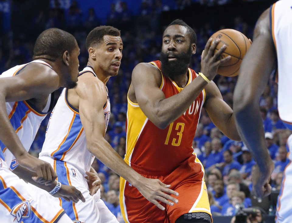 Photo - Houston Rockets guard James Harden (13) drives past Oklahoma City Thunder forward Kevin Durant, left, and guard Thabo Sefolosha during the first quarter of Game 5 of a first-round NBA basketball playoff series in Oklahoma City, Wednesday, May 1, 2013. (AP Photo/Sue Ogrocki)