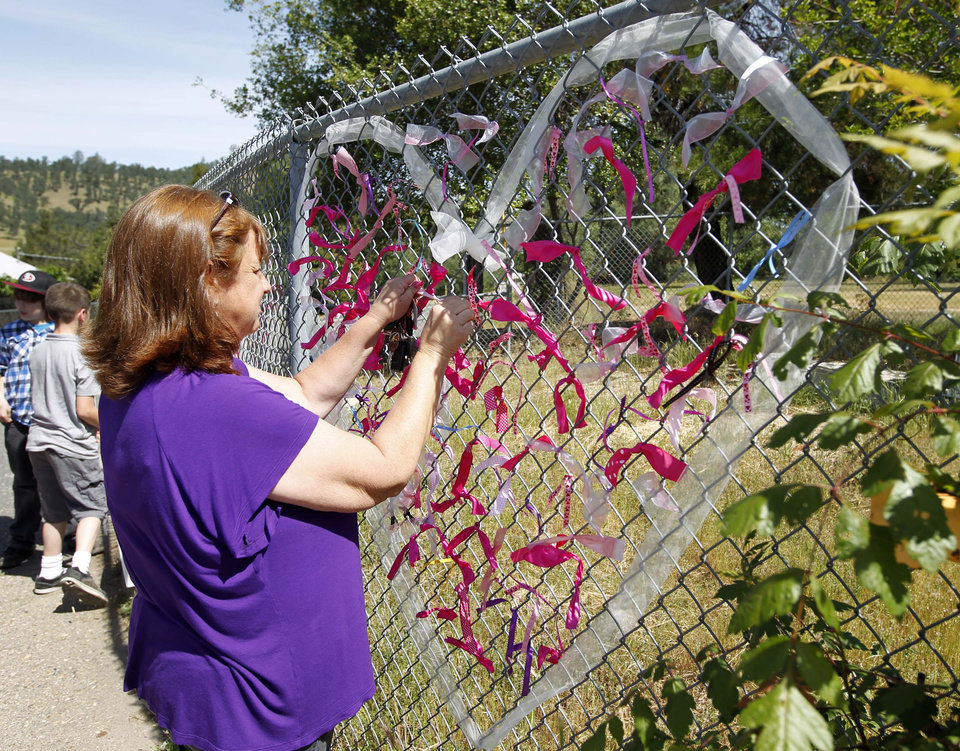 Photo - Teacher Cecilia Richardson ties a ribbon honoring murder victim honoring murder victim, Leila Fowler, at Jenny Lind Elementary School in Valley Springs, Calif., Monday April 29, 2013. Authorities are searching for the killer of  Fowler, 8, who was found murdered by her 12-year-old brother in the family's Valley Springs home Saturday. (AP Photo/Rich Pedroncelli)
