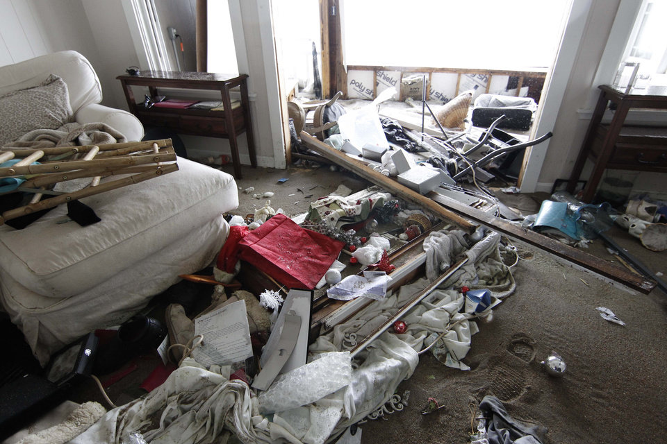 Photo - Debris is piled up in a house which was hit by a wave and flooded in Salisbury, Mass. on Saturday, Feb. 9, 2013. A behemoth storm packing hurricane-force wind gusts and blizzard conditions swept through the Northeast overnight. (AP Photo/Winslow Townson)