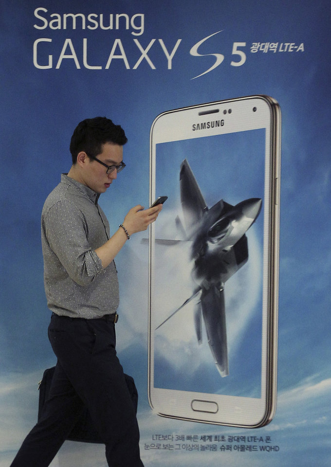 Photo - A man walks by an advertisement of Samsung Electronics' Galaxy S5 smartphone at the company's showroom in Seoul, South Korea, Thursday, July 31, 2014. Samsung Electronics Co. reported a bigger-than-expected fall in second quarter profit on Thursday and said it was uncertain if earnings from its handset business would improve in the current quarter.(AP Photo/Ahn Young-joon)