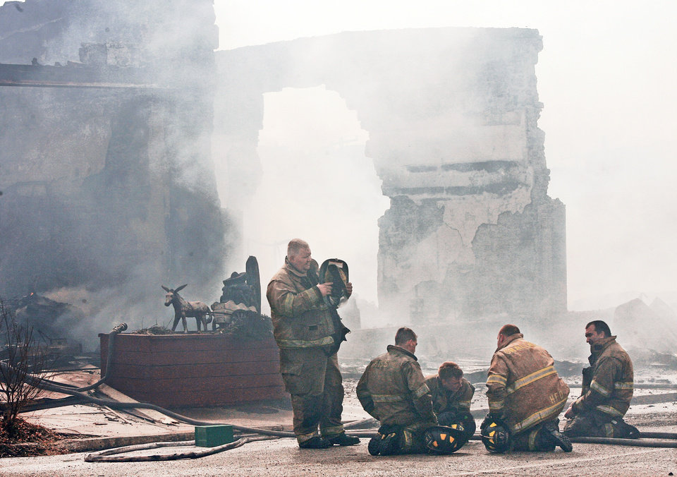 Photo - Firefighters rest Friday after bringing the worst part of the blaze under control.  Firefighters from several communities assisted crews from Weleetka in battling a large blaze that destroyed a block of downtown businesses.  PHOTO BY JIM BECKEL, THE OKLAHOMAN