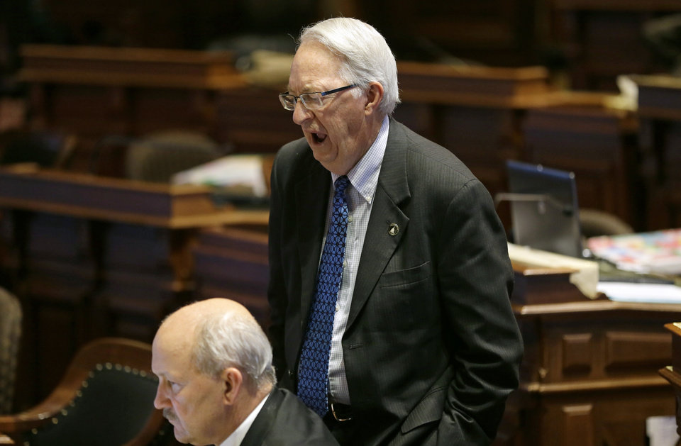 Photo - Sen. Dennis Black, D-Grinnell, lets out a yawn as he talks with Sen. Bill Dotzler, D-Waterloo, left, on the floor of the Senate, Thursday, May 1, 2014, at the Statehouse in Des Moines, Iowa. The Iowa Senate, after working all night to finish the 2014 legislative session, must return for one more day after a dispute developed involving subpoena powers. (AP Photo/Charlie Neibergall)