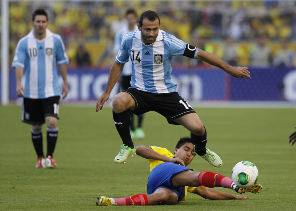 Photo - FILE - In this June 11, 2013, file photo, Argentina's Javier Mascherano, center, jumps over Ecuador's Christian Noboa during a 2014 World Cup qualifying soccer match in Quito, Ecuador.  (AP Photo/Dolores Ochoa, File)