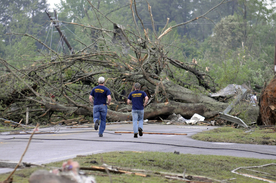 Photo - Concord Fire and Rescue personel run toward a large down tree that was blocking Warrior River Road after a tornado touched down, Wednesday, April 27, 2011 in Concord, Ala.  (AP Photo/Birmingham News, Jeff Roberts) M
