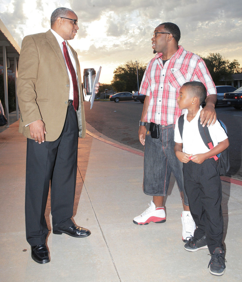 "Organizer Calvin Williams visits Friday with Markis Frederick and his son, Tishaun, 6, during ""Take Your Child to School Day"" at Martin Luther King Elementary School. Photos By David McDaniel, The Oklahoman"