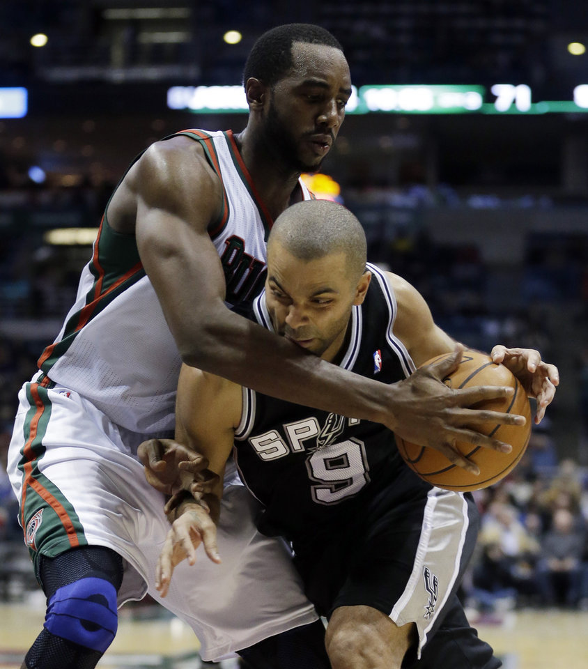 Photo - San Antonio Spurs' Tony Parker (9) tries to drive past Milwaukee Bucks' Luc Richard Mbah a Moute during the second half of an NBA basketball game on Wednesday, Jan. 2, 2013, in Milwaukee. (AP Photo/Morry Gash)