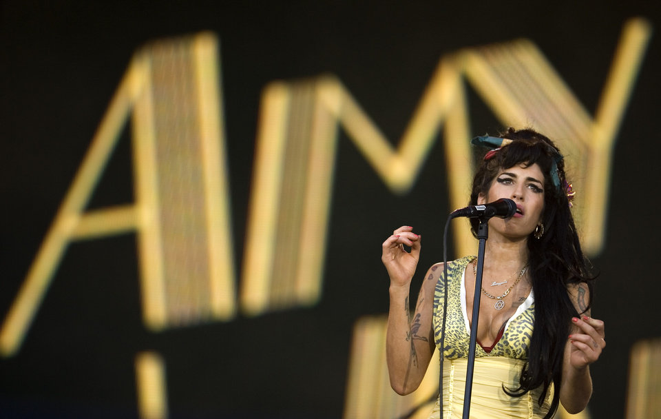 Photo - FILE - In this July 4, 2008 file photo, singer Amy Winehouse performs during the Rock in Rio music festival in Arganda del Rey, on the outskirts of Madrid. A second coroner's inquest confirmed Tuesday Jan. 8, 2013, that Amy Winehouse died of accidental alcohol poisoning when she resumed drinking after a period of abstinence. The second inquest was held after the original coroner was found to lack the proper qualifications for the job. (AP Photo/Victor R. Caivano, File)