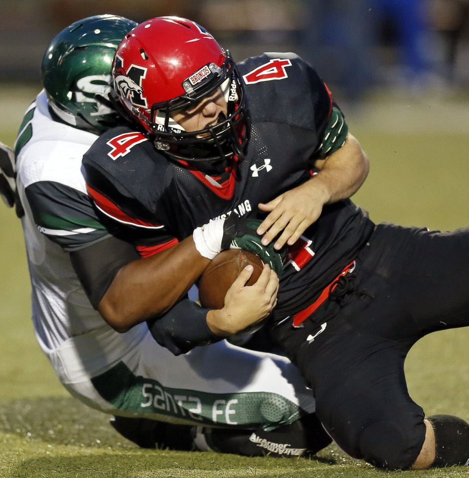 Edmond Santa Fe's Alvin Bazley (41) brings down Mustang quarterback Frankie Edwards (4) during a high school football game between Mustang and Edmond Santa Fe in Mustang, Okla., Friday, Sept. 28, 2012. Photo by Nate Billings, The Oklahoman