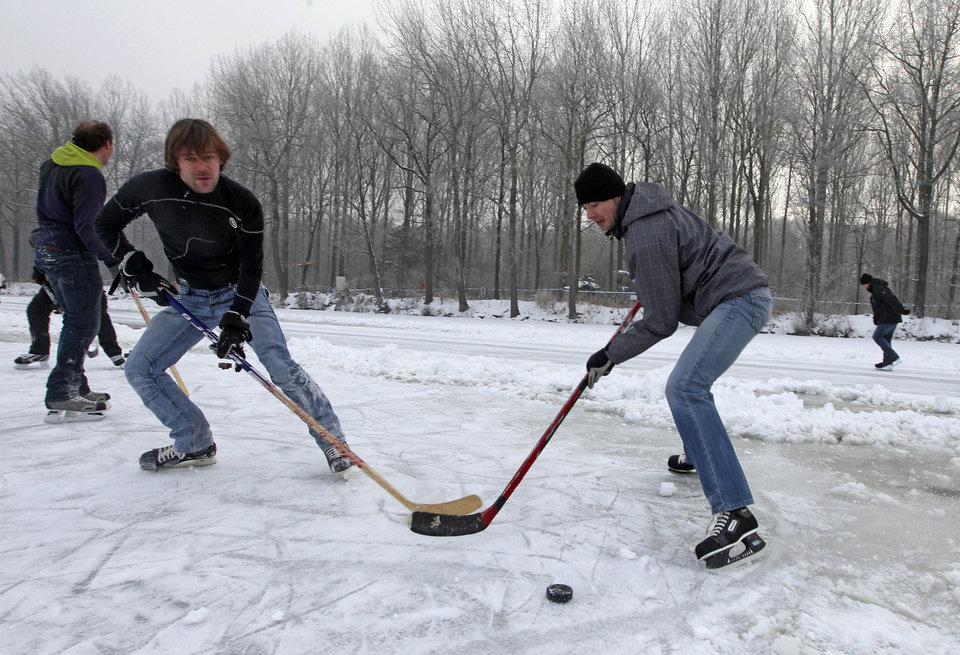 Men play ice hockey on a frozen pond in Aalter, 75 kilometers (47 miles) west of Brussels, Wednesday, Jan. 23, 2013. Belgium has been in the grip of cold and snowy weather for a week. (AP Photo/Yves Logghe)
