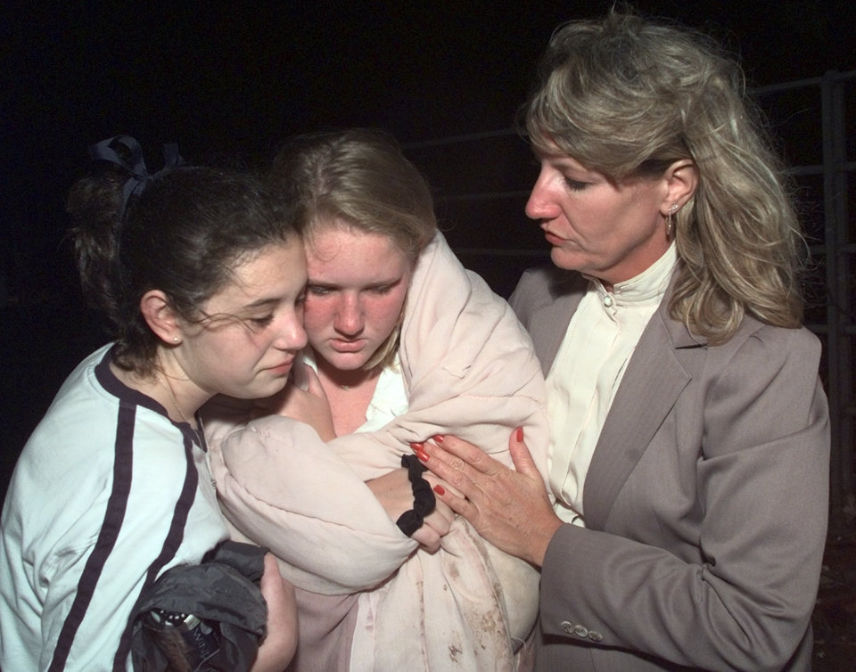 May 3, 1999, Oklahoma City Tornado:  Tornado victims: Maggie Blice, sophomore at Westmoore (center)is comforted by Tonya Martin and her mother Peggy Blice after exiting Westmoore High School auditorium.  All were attending an awards ceremony in the school when the tornado struck.  Staff Photo by Steve Sisney