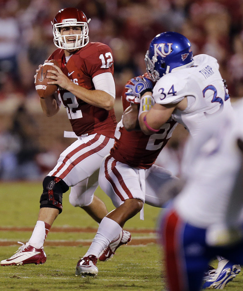 Photo - OU's Landry Jones (12) looks to pass the ball against Kansas during the college football game between the University of Oklahoma Sooners (OU) and the University of Kansas Jayhawks (KU) at Gaylord Family-Oklahoma Memorial Stadium on Saturday, Oct. 20th, 2012, in Norman, Okla. Photo by Chris Landsberger, The Oklahoman
