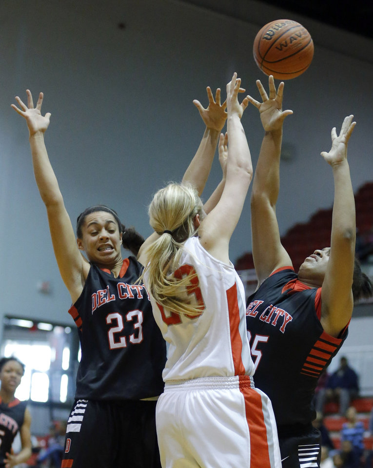Photo - Carl Albert's Asher Sutterfield pass the ball over Del City's Breail Goodlow and Shaletha Clark, right, during the girl's basketball game between Del City and Carl Albert at Carl Albert High School,  Saturday, Feb. 23, 2013. Photo by Sarah Phipps, The Oklahoman