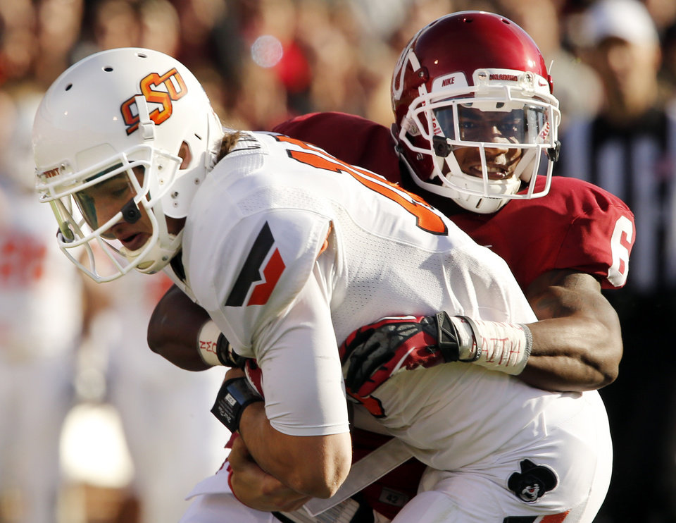 Oklahoma\'s Demontre Hurst (6) brings down Oklahoma State\'s Clint Chelf (10) after a long gain during the Bedlam college football game between the University of Oklahoma Sooners (OU) and the Oklahoma State University Cowboys (OSU) at Gaylord Family-Oklahoma Memorial Stadium in Norman, Okla., Saturday, Nov. 24, 2012. Photo by Steve Sisney, The Oklahoman