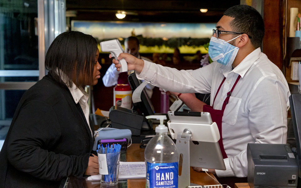 Photo - Employee Josh Mijares takes the temperature of employee Kari Ivey at Cattlemen's Steakhouse in Oklahoma City, Okla. on Friday, May 1, 2020. All members of the staff sign in and have their temperature taken before starting their shift as the restaurant begins its gradual reopening on Friday after being closed due to the Coronavirus Pandemic.[Chris Landsberger/The Oklahoman]