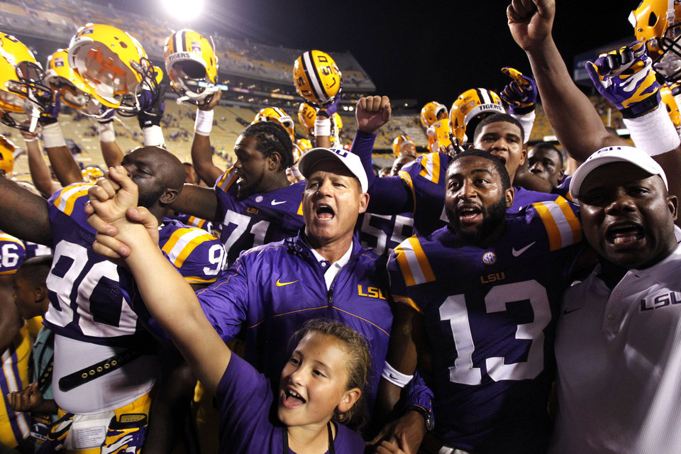 Photo -   LSU head coach Les Miles center, sings the LSU alma mater with his daughter Macy Miles, below, and his team, after their NCAA college football game against Idaho in Baton Rouge, La. Saturday, Sept. 15, 2012. LSU won 63-14. (AP Photo/Gerald Herbert)