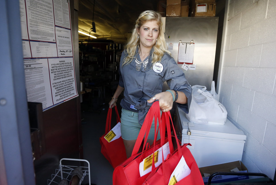 Photo - In this June 19, 2014 photo, production team member Alexa R. carries bags of boxed cannabis-infused confections to a delivery vehicle making a supply run, at Sweet Grass Kitchen, a well-established gourmet marijuana edibles bakery which sells to retail outlets, in Denver. Sweet Grass Kitchen, like other cannabis food producers in the state, is held to rigorous health inspection standards, and has received praise from inspectors, according to owner Julie Berliner. (AP Photo/Brennan Linsley)