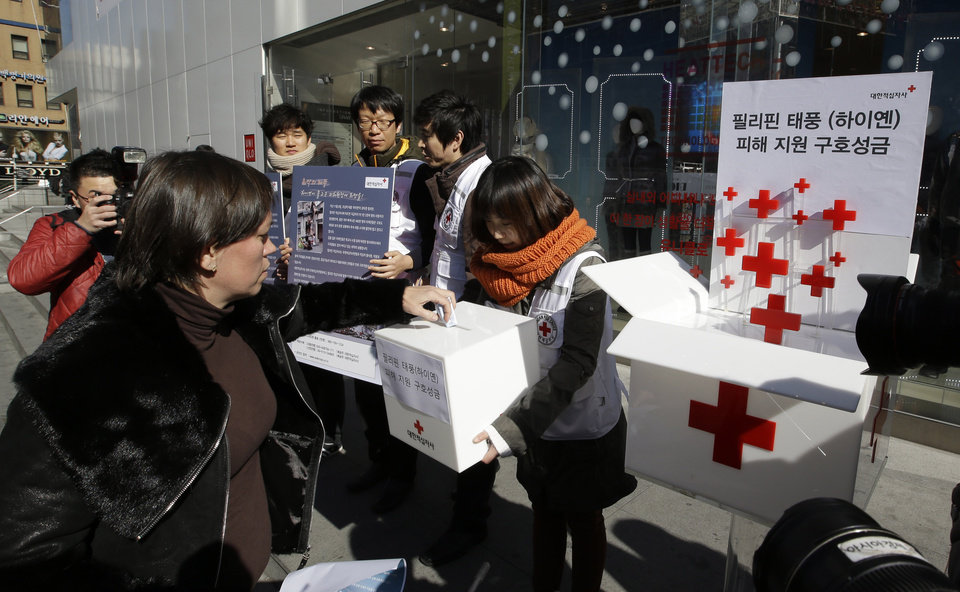 Photo - FILE - In this Wednesday, Nov. 13, 2013 file photo, a tourist donates money for the victims of Typhoon Haiyan in the Philippines during a fund-raising campaign on a street in Seoul, South Korea. Signs read,