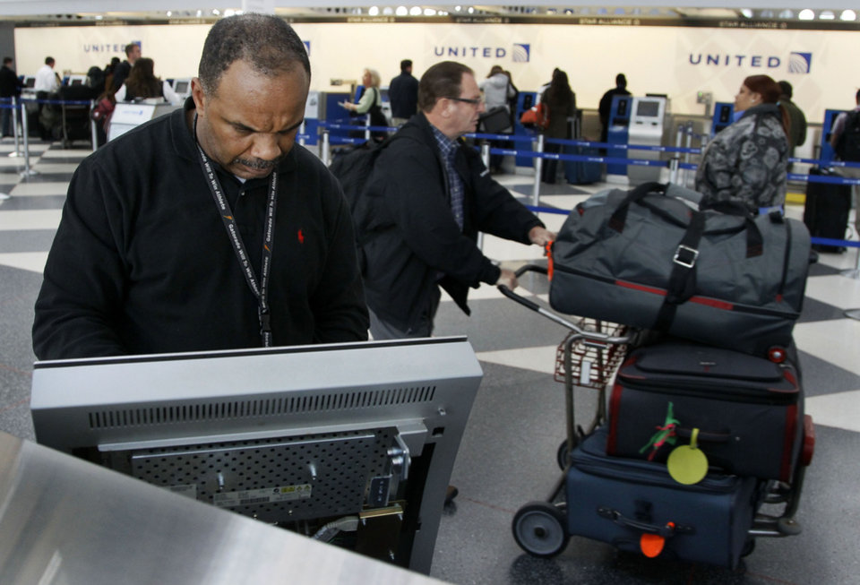 Photo -   David Caradine works at upgrading the software at a United Airlines e-ticket kiosk at Chicago's O'Hare International Airport Thursday, Nov. 15, 2012. Passengers in several cities say a massive computer outage has stranded United passengers at airports across the country, resulting in at least the third major computer outage for the Chicago-based airline since June. (AP Photo/Charles Rex Arbogast)