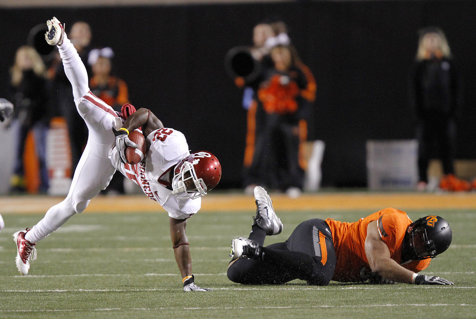 Oklahoma\'s Roy Finch (22) is upended by Oklahoma State\'s Jamie Blatnick (50) during the Bedlam college football game between the Oklahoma State University Cowboys (OSU) and the University of Oklahoma Sooners (OU) at Boone Pickens Stadium in Stillwater, Okla., Saturday, Dec. 3, 2011. Photo by Chris Landsberger, The Oklahoman