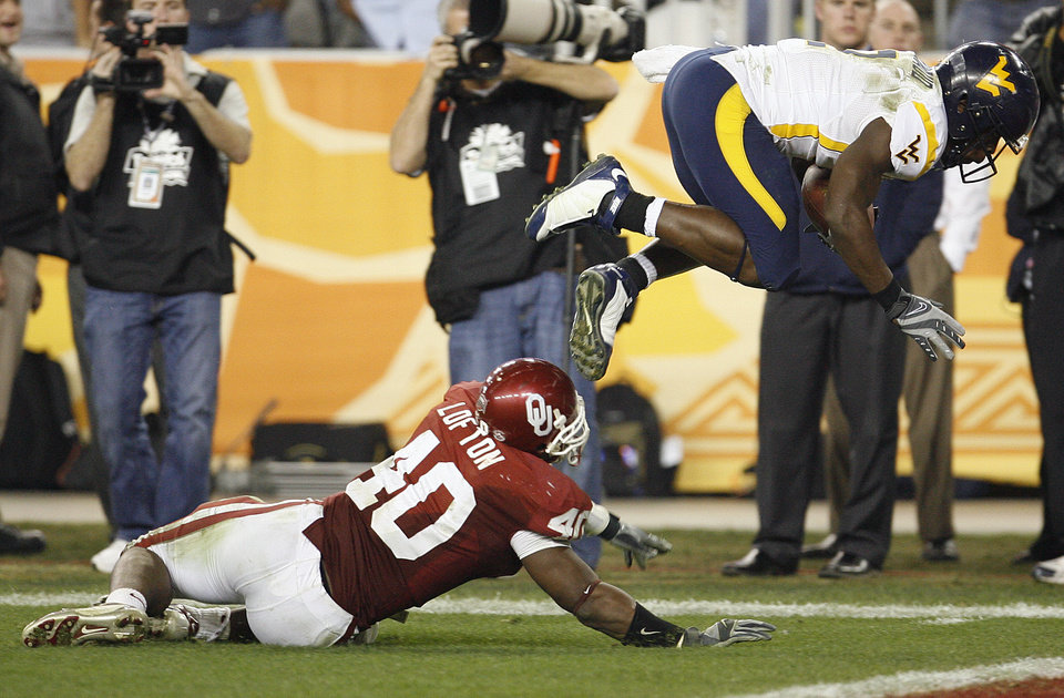 Photo - West Virginia's Darius Reynaud (2) dives into the endzone for a touchdown past Oklahoma's Curtis Lofton (40) during the second half of the Fiesta Bowl college football game between the University of Oklahoma Sooners (OU) and the West Virginia University Mountaineers (WVU) at The University of Phoenix Stadium on Wednesday, Jan. 2, 2008, in Glendale, Ariz. 