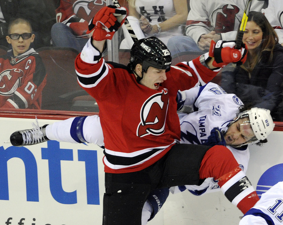 New Jersey Devils' Cam Janssen (25) checks Tampa Bay Lightning's Cory Conacher during the second period of an NHL hockey game Tuesday, March 5, 2013, in Newark, N.J. (AP Photo/Bill Kostroun)