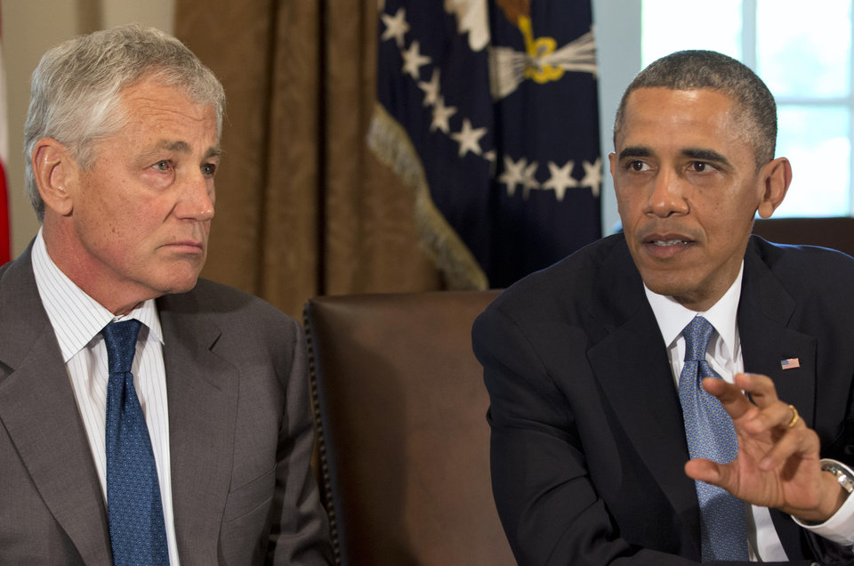 Photo - Defense Secretary Chuck Hagel listens as President Barack Obama speaks during a meeting to discuss sexual assault in the military in the Cabinet Room of the White House in Washington, Thursday, May 16, 2013. (AP Photo/Jacquelyn Martin)