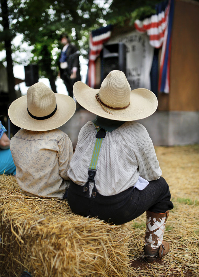 Conagher Hardaway, 7, left, and his cousin, Nathan Buck Allison, 9, sit on hay bales to watch performance by Dr. H. P. Hedgethicket III, Esquire, the character played by George Hopkins of Oklahoma City, in his recreation of an 1880s traveling Medicine Show at the 2014 Chuck Wagon Gathering and Children's Cowboy Festival hosted by the National Cowboy & Western Heritage Museum on NE 63 Street in Oklahoma City on Saturday,  May 24, 2014.  The festival continues on Sunday, May 25, from 10 a.m. to 4 p.m. Hardaway is from Foss, OK. Allison is from South Coffeyville, OK. Photo by Jim Beckel, The Oklahoman
