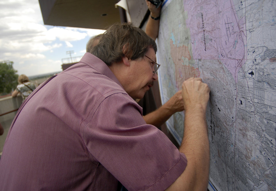 Photo -   Waldo Canyon Fire evacuee Bill Myers looks for his street on a map at the Cheyenne Mountain High School evacuation center on Wednesday, June 27, 2012, in Colorado Springs, Colo. The wildfire doubled in size overnight to about 24 square miles (62 square kilometers), and has so far forced mandatory evacuations for more than 32,000 residents. (AP Photo/Bryan Oller)