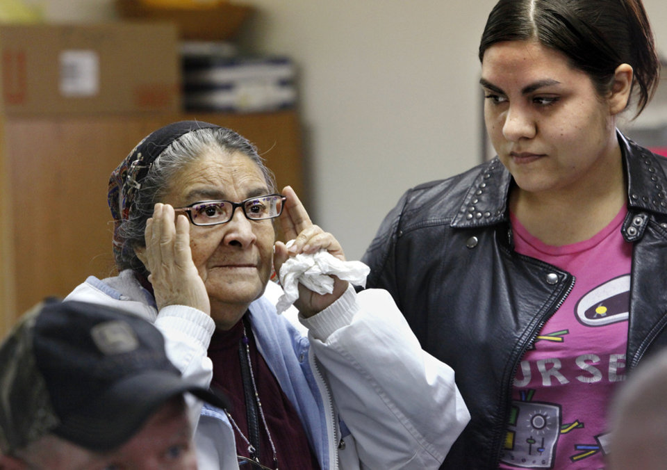 Photo - Guadalupe Fuentes, left, adjusts a new set of eyeglasses as she reads an eye chart to her daughter, Rosa Rodriguez, as Fuentes tries different pairs of glasses. Photos by Jim Beckel, The Oklahoman