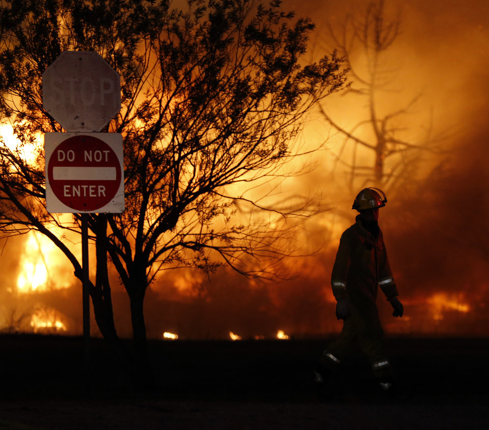 Photo - A firefighter walks through a burning mobile home park near Prairie Grove Rd. and Douglas during wildfires in Logan County, Sunday, May 4, 2014. Photo by Nate Billings, The Oklahoman