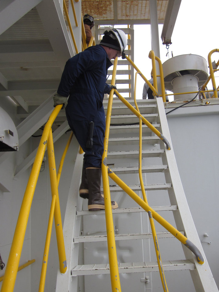 Photo - This Jan. 10, 2013, photo provided by the U.S. Coast Guard shows an inspector climbing damaged stairs during an inspection aboard the Shell Arctic drilling rig Kulluk in Kiluida Bay, near Kodiak, Alaska. The rig grounded on Sitkalidak Island on Dec. 31, 2012, and was towed to Kiliuda Bay Jan. 7, 2013. The unified command overseeing salvage of the rig says it will release minimal information on the vessel until an assessment is complete. (AP Photo/U.S. Fish and Wildlife Service)