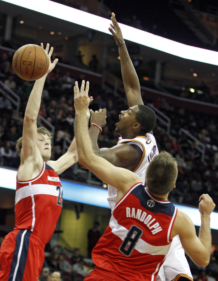 Cleveland Cavaliers\' Tristan Thompson (13) loses control of the ball under pressure from Washington Wizards\' Jan Vesely (24) and Shavlik Randolph (8) during the second quarter of an NBA preseason basketball game Saturday, Oct. 13, 2012, in Cleveland. (AP Photo/Tony Dejak)