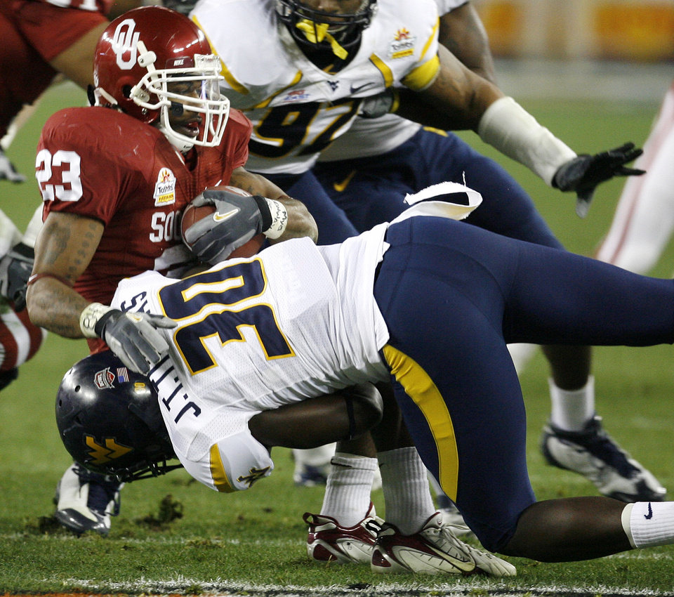 Photo - Allen Patrick (23) is brought down by West Virginia's J.T. Thomas (30) during the first half of the Fiesta Bowl college football game between the University of Oklahoma Sooners (OU) and the West Virginia University Mountaineers (WVU) at The University of Phoenix Stadium on Wednesday, Jan. 2, 2008, in Glendale, Ariz. 