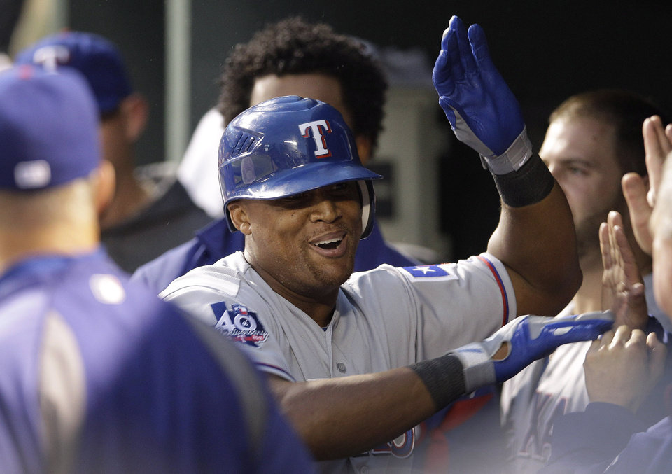 Photo -   Texas Rangers' Adrian Beltre high-fives teammates in the dugout after hitting a solo home run in the third inning of a baseball game against the Baltimore Orioles in Baltimore, Tuesday, May 8, 2012. (AP Photo/Patrick Semansky)