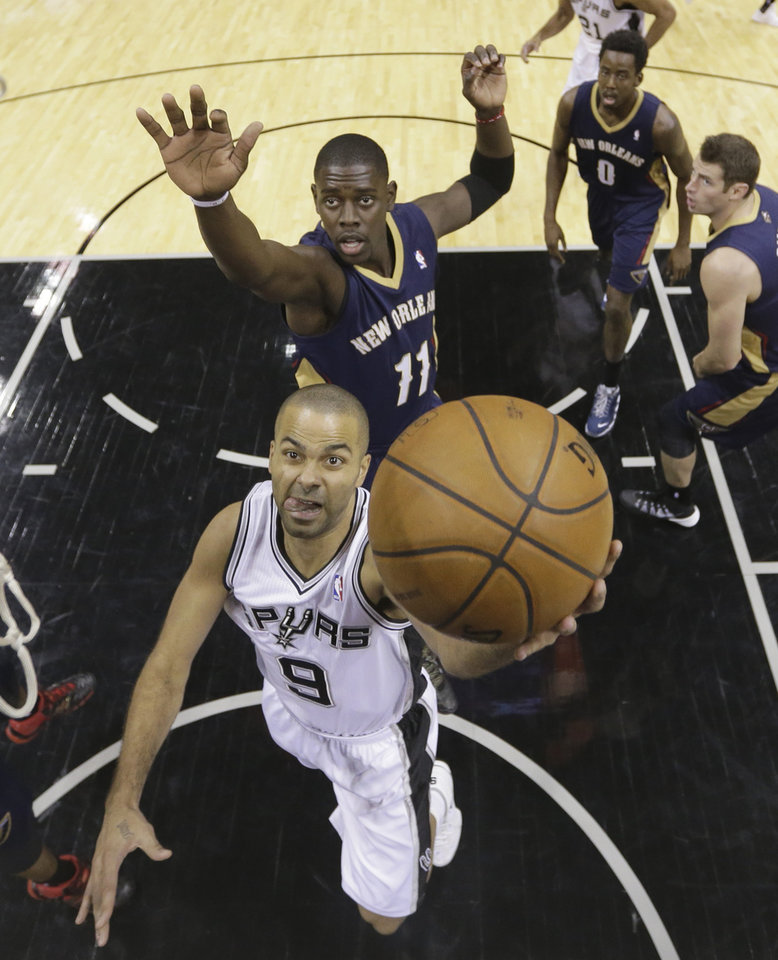 Photo - San Antonio Spurs' Tony Parker (9), of France, scores in front of New Orleans Pelicans' Jrue Holiday (11) during the first half of an NBA basketball game, Monday, Nov. 25, 2013, in San Antonio. (AP Photo/Eric Gay)