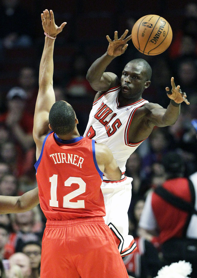 Chicago Bulls forward Luol Deng, right, passes the ball as Philadelphia 76ers forward Evan Young guards during the first half of an NBA basketball game in Chicago on Saturday, Dec. 1, 2012. (AP Photo/Nam Y. Huh)